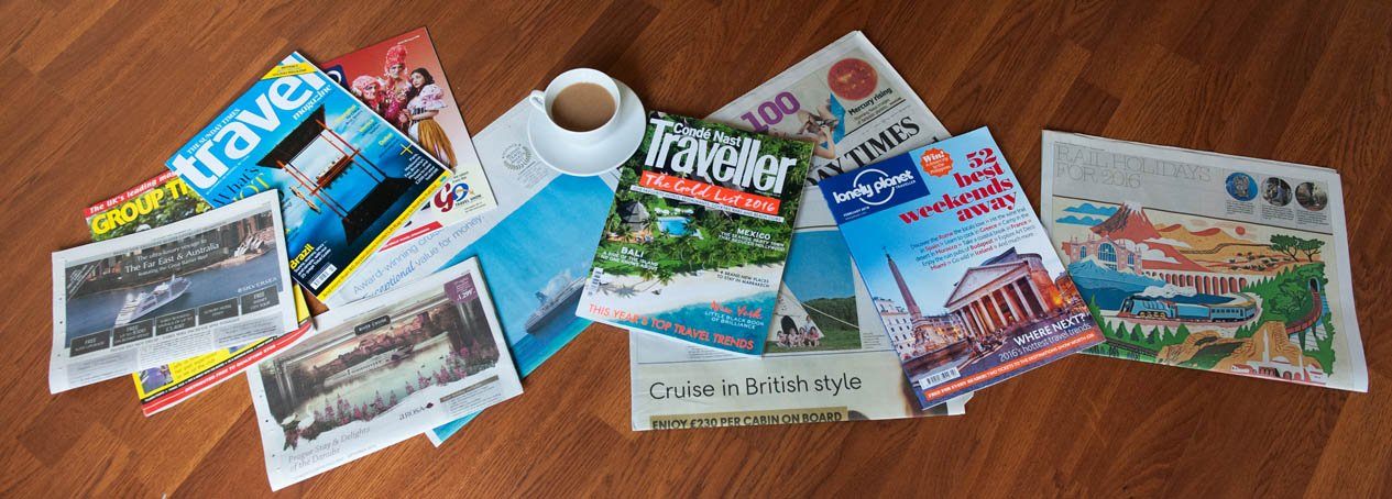Travel magazines spread out on a table