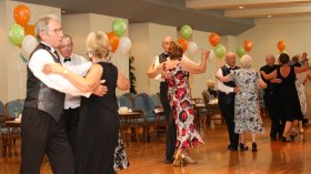 A group of holidaymakers sequence dancing